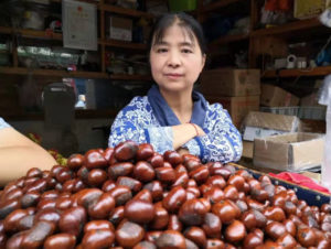 woman standing behind chestnuts