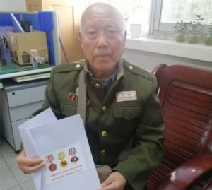 veteran sitting down holding medals