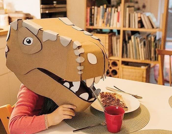 child sitting at table wearing dinosaur head made from cardboard