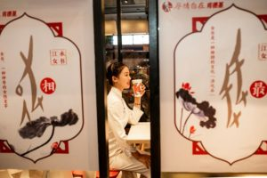 side view of woman sitting at cultural themed KFC in china