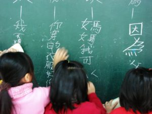 children writing mandarin language characters on chalkboard