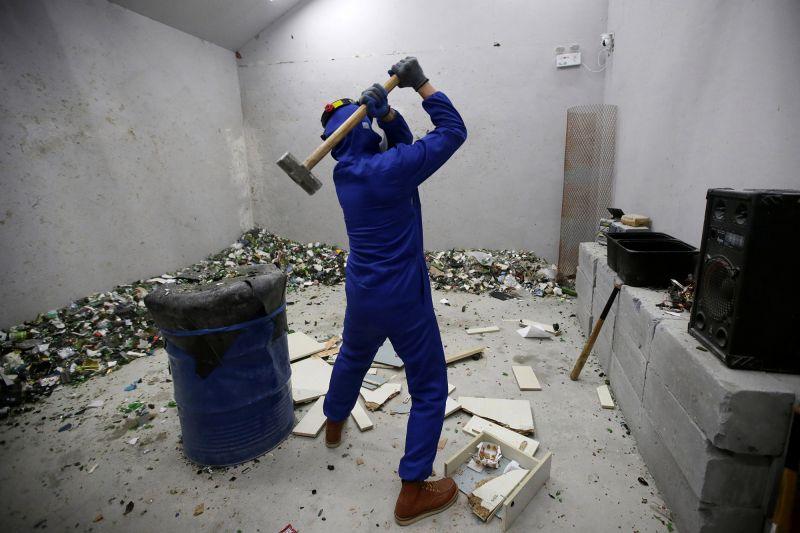man smashing things in anger room