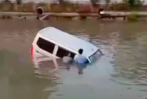 two men next to car in river