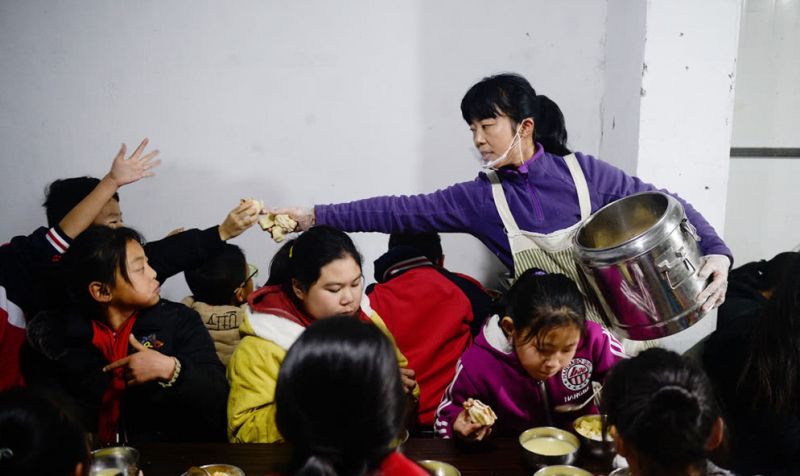 woman handing out food to children