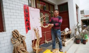 man with root carved sculptures