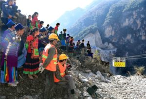 workers and villagers watching cable car in moutains