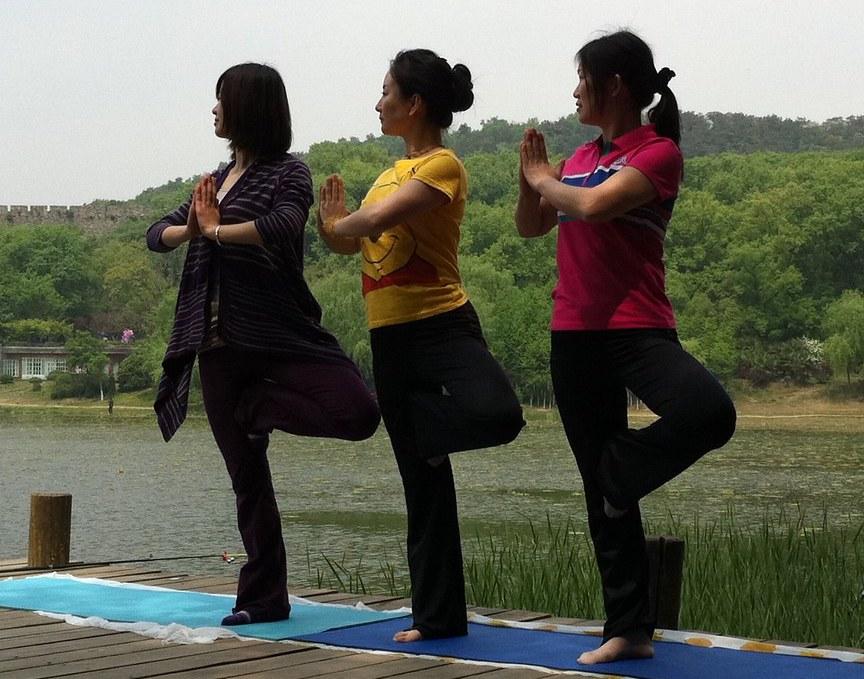three women striking yoga pose outside