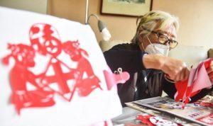 elderly man wearing face masks and making paper cutting art
