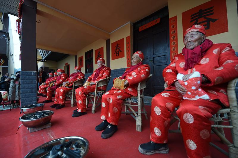 elderly people wearing red and sitting in a line
