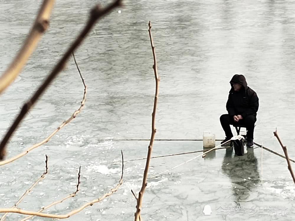 man fishing on frozen lake