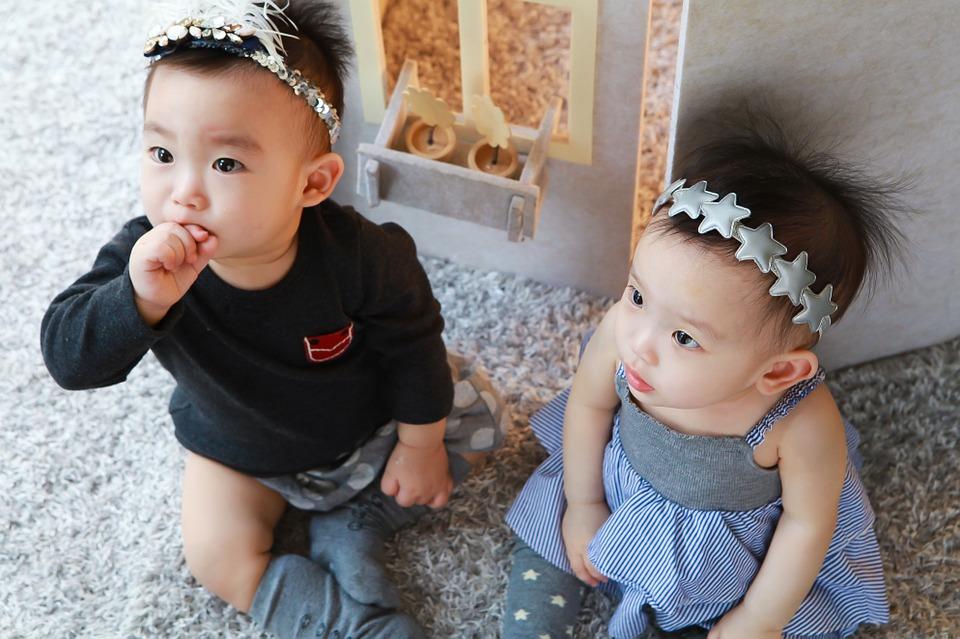two babies sitting on floor