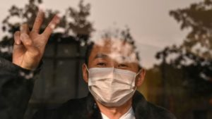 man behind window wearing mask and making peace sign