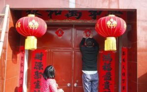 father and daughter decorating door for CNY