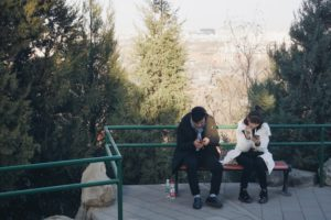 gestures ; couple sitting on a bench