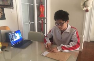 student sitting at table opening mail