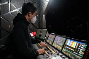 side view of DJ wearing mask in DJ booth