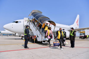 workers disembarking plane wearing face masks