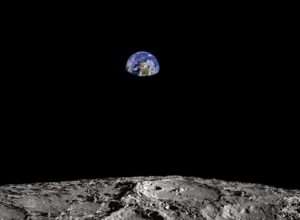 surface of moon with earth in the distance