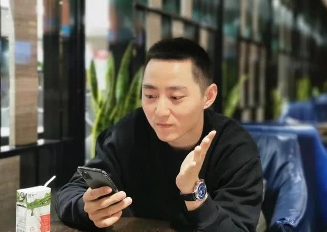 man sitting at table and looking at phone