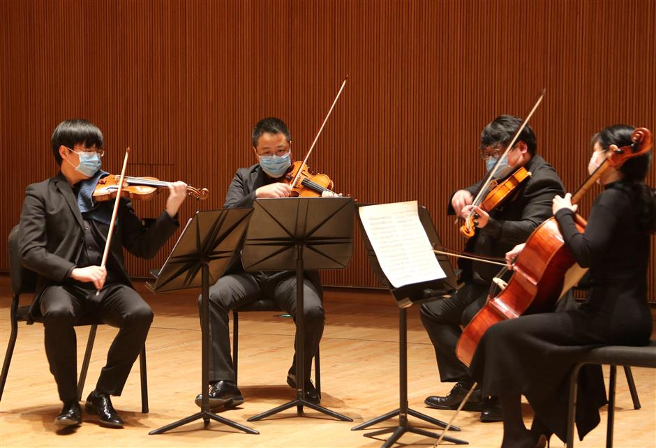 members of shanghai symphony orchestra performing while wearing face masks
