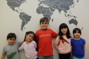 students standing in front of world map