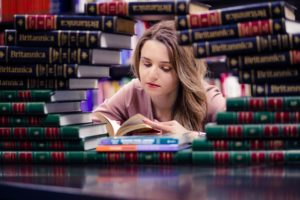 girl studying surrounded by books