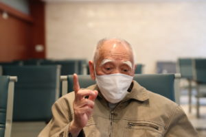 elderly man wearing mask with finger in the air in china