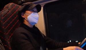 female driver wearing mask behind wheel
