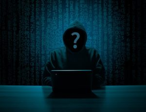 hacker using computer with code in background