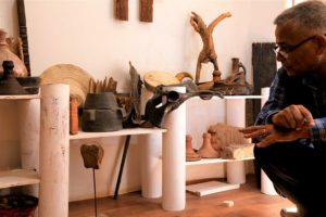 man squatting next to hand-made art collection
