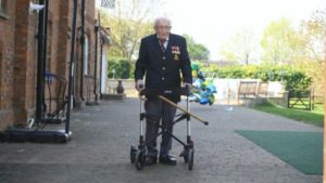 front view of elderly war veteran pushing wheelchair in garden