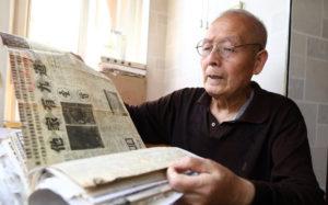 elderly man holding newspaper in china
