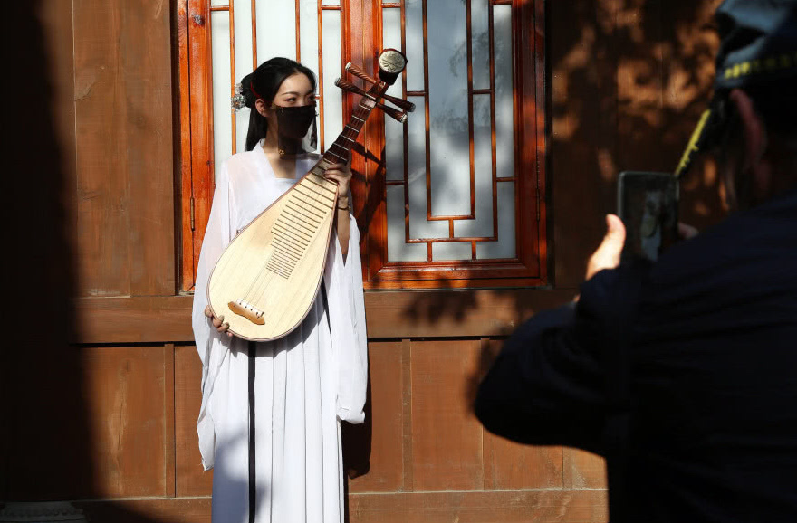 tourist taking picture of girl holding chinese lute