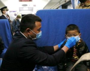 train attendant helping child with mask