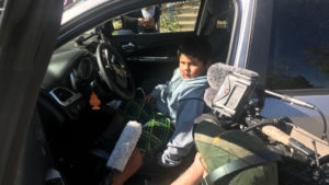 side view of boy in drivers seat of car