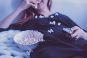 chinese dating shows : girl with remote in hand whilst eating popcorn