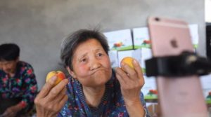 elderly woman holding apricots on live broadcast