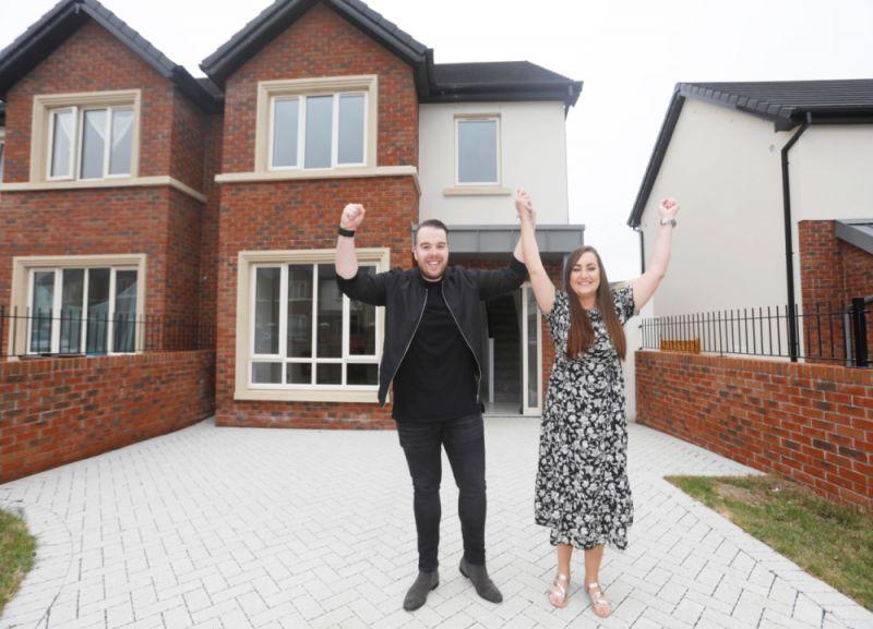 couple raising arms outside house
