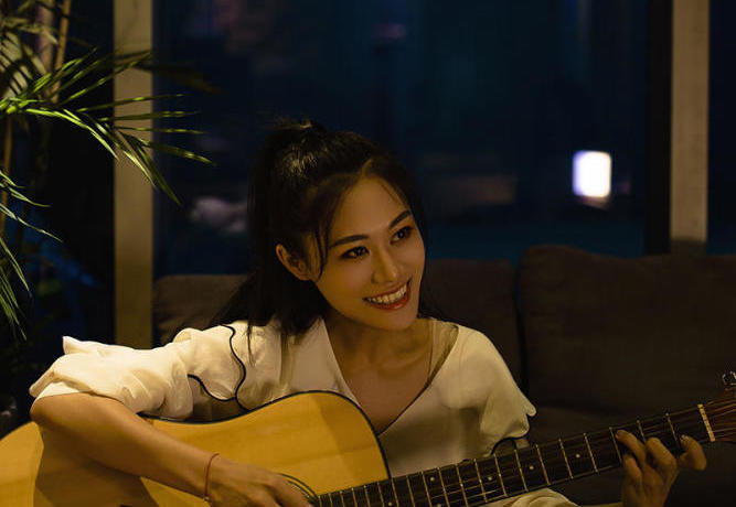 girl smiling and playing guitar