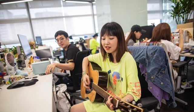 girl playing guitar in office in china