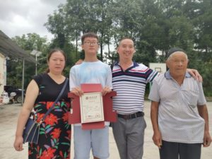boy with family holding university acceptance certificate in china