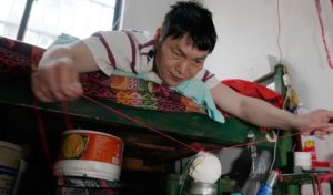man lying on bed and stitching baseball in china