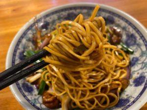 chopsticks and a bowl of noodles