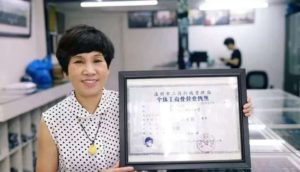 woman holding business license from 1980s in china