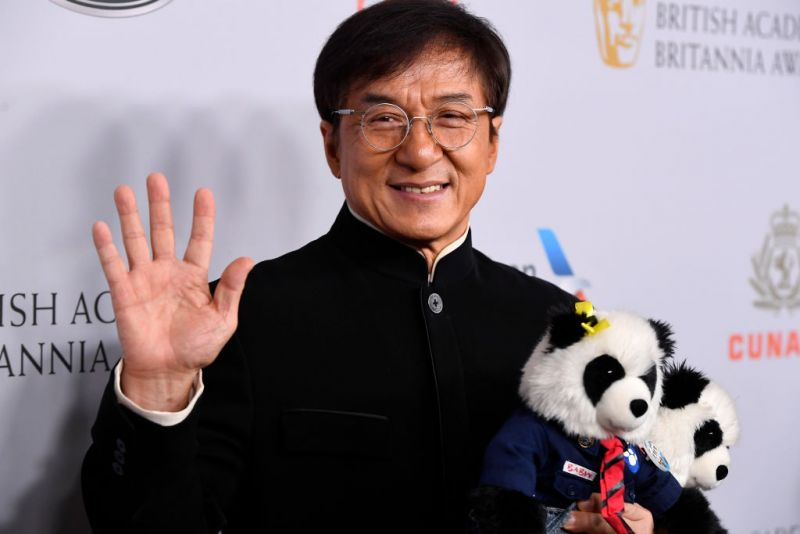 jackie chan holding toy pandas and posing for picture