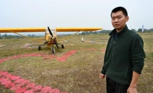 farmer standing next to home-made airplane in china
