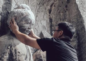 man placing 3D-printed head of buddhist statue in china