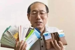 man posing with wallet and coupons in japan