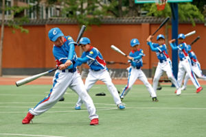 children practicing baseball in china