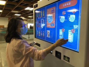 woman buying masks from vending machine on shanghai metro